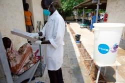Juba Teaching 病院で簡易ベッドに横たわる人に話しかけるヘルスワーカー