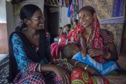 子どもの栄養やケアの方法について、母親たちの相談にのったり、アドバイスをしたりするボランティアの女性(インド)