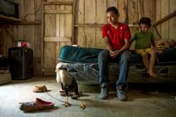 ホンジュラスのオモアにある自宅で過ごす、アレクシスさん(18歳)、ウィルソンくん(6歳)、飼っているカラカラ。