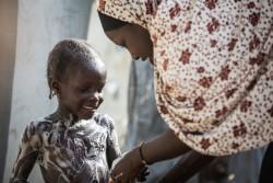 ダルエスサラームの難民キャンプで妹の世話をするハディージャさん(15歳)