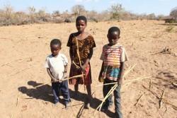マタベレランド・サウスの村で、畑が干上がって実がならなかった作物を手にするメロディ・ンデベレさん(13歳)と兄弟たち。(2016年8月25日撮影)