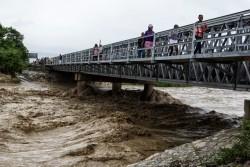 ハリケーン・マシュー通過後に、橋の上から水量が増した川を見る人々。(ポルトープランス 2016年10月4日撮影)
