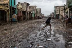 ハリケーン・マシューは、激しい雨と風をもたらしながらハイチを通過した。ポルトープランスの繁華街の通りを渡る女性。(2016年10月4日撮影)