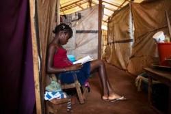 中央アフリカ共和国の国内避難民が身を寄せるキャンプで、本を読むアリソンさん(14歳)