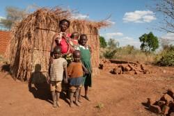 干ばつによる食糧不足の影響を受けるマラウイで、2歳、6歳、8歳、10歳の子どもと、トウモロコシの皮で作られた家族の住む小屋の前に立つアリナフェさん(マラウイ・バラカ州 2016年6月28日撮影)。