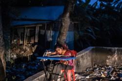 学校から帰った後、母親が拾い集めた物を売るのに使う机で勉強する、ジュマさん(14歳)。8歳で学校をやめ、3年間住み込みのお手伝いとして働いている間は、学校にも行けなかった。(バングラデシュ・クルナ 2016年3月29日撮影)