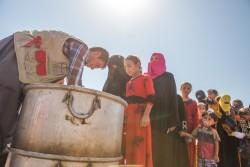 イラク・モスルの避難民キャンプで、支援物資を受け取る避難民の子どもと女性。(2016年10月3日撮影)