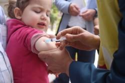 予防接種キャンペーンで移動保健チームから予防接種を受けるアレッポの子ども(2016年4月撮影)