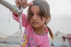 避難民キャンプで水を汲む、モスルから逃れてきた女の子。(2016年11月15日撮影)