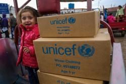 イラク・エルビルにある難民キャンプで支援物資の隣に笑顔で立つ、シリア人の女の子。(2016年12月1日撮影)