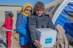 モスルから避難民キャンプに到着し、水などの支援物資を受け取る女の子たち。