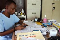 携帯端末からRapidProを通じて、到着した薬や医薬品のレポートを行う保健員。