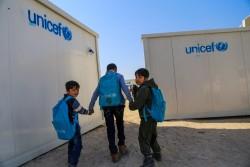 イラクのアンバール県ファルージャで、一時的な教室として使用されているトレーラーハウスの間を通り過ぎる、アーメッドくん(6歳・写真左)、オサマくん(7歳・写真右)。