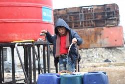 アレッポ東部にユニセフが設置した給水所に行き、水をポリタンクに入れる男の子。ユニセフは毎日トラックで給水所に水を運搬している。