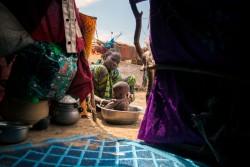 ナイジェリア・ボルノの国内避難民キャンプで子供を洗う女性。(2016年11月9日撮影)