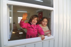トルコ・ガズィアンテプの難民キャンプにある教室の窓から手を振る女の子たち。(2017年1月16日撮影)