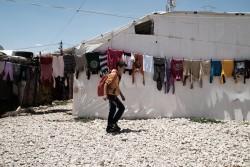非公式居住地に干された洗濯物の列を通り過ぎながら、学校に通うシリア難民の男の子(レバノン、ベッカー高原)