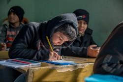 モスル東部の再開された学校で授業を受ける男の子。(