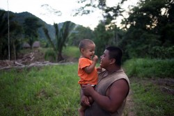 "On 15 August 2016 in Belize, 2-year-old Abner laughs while being carried by his father, James Choc, outdoors on their family's plot of land, in San Felipe Village in the Toledo region. The family, which consists of Abner's parents, grandparents and aunt – participates in the Roving Caregivers Programme (RCP), which brings services to vulnerable families in the region, especially those living in distant and hard-to-reach locations. Just 50 per cent of villages in the remote, predominately Mayan communities in the Toledo region have access to preschool or day-care services for their children. With many caregivers – including Abner's parents and grandfather – working on plantations or construction sites, young children are at risk of missing out on stimulating interaction, a key element for their development. The UNICEF-supported programme, targets children up to age three who have no access to formal early childhood education. RCP facilitators (known as 'Roving Caregivers' or Rovers), who are trained members of the local community, conduct 45-minute home outreach with each of the families they serve, engaging children in age-appropriate stimulating activities through play and encouraging parents and caregivers to participate. They also encourage positive parenting behaviour; and promote behaviour change to address inappropriate parenting practices The 22 Rovers in the RCP programme conduct 45-minute outreach visits with each family. ""My favourite part of my children's lives was when they were young and playing without worry; they were laughing and smiling and growing,"" said Abner's grandmother, Maria Choc (not pictured), a mother of 13. In recent years, considerable progress was made in the area of Early Childhood Development. In 2011 only 32 per cent of children between 36 and 59 months of age attended an Early Childhood Education (ECE) programme, but this reached 55 per cent by 2015. Disparities however persist as only one in five of the p"