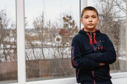 学校に残る銃痕の脇に立つ男の子(ウクライナ・ドネツク州)