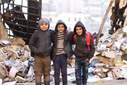 アレッポ東部で2年ぶりに学校が再開され、校門の向かいに立つ子どもたち。