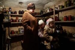 砲撃の間、薄暗い地下室に隠れる家族(ウクライナ・ドネツク州)