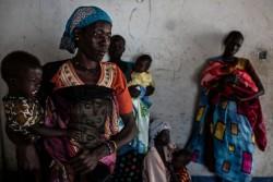 南スーダン北部の村で、移動式クリニックを訪れ、子どもの健康状態のチェックを待つ女性たち。