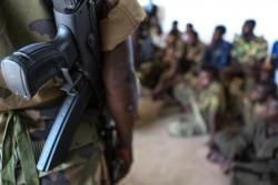 南スーダンの首都バンギで、武装グループから解放された子どもたちのそばに立つ兵士