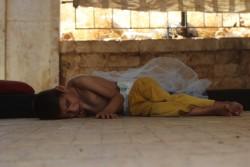 攻撃から逃れ、アレッポ西部の路上で生活する脊髄性筋萎縮症を患う男の子
