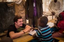 国内避難民の子どもたちのための一時学習スペースで生徒と話すオーランド・ブルームユニセフ親善大使(2017年2月17日撮影)