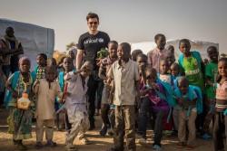 教室に向かう子どもたちと一緒に歩くオーランド・ブルームユニセフ親善大使(2017年2月17日撮影)