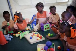 Children play with Early Childhood Development (ECD) kits inside a UNICEF tent at St Benedict school, in a IDP camp located in a former golf course. Since March 2010, over 1.495 kits have been distributed by UNICEF throughout  the country to support Haitian Ministry of Education and NGO partners in maintaining childhood development programs.