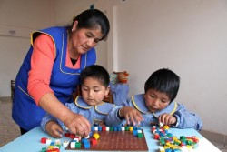 A caregiver helps two small children during a learning activity with blocks, at the Sayariy Warmi early childhood development (ECD) centre in Sucre, the capital. UNICEF supports ECD centres throughout the country. In December 2013 in Bolivia, economic growth and government investment in basic social services continue to improve the lives of children and families. The country has achieved many Millennium Development Goals (MDGs), including regarding extreme poverty, malnutrition, literacy, and gender equality; and a number of others are also on track. However, despite notable progress that includes increased safe water and sanitation access, reduced infant mortality and a decline in chronic malnutrition among children under age three, challenges remain. Income, geographical and other disparities persist, particularly in rural communities. Despite a low unemployment rate, poverty remains high –with 45 per cent of the population living below the national poverty line. According to most data currently available, 11 per cent of children between the ages of 5 and 13 are involved in some form of labour, irrespective of their gender, with children sometimes working in dangerous conditions in the country's harshest jobs – such as mining – to help support their families. Challenges in preschool and secondary education are many, although education and other social expenditures on behalf of children have increased. Current available maternal mortality rates are high, and neonatal mortality has little changed. The country also still lags behind in ensuring children's right to an identity, especially in vulnerable communities. Working with the Government and United Nations and other partners, UNICEF supports health, hygiene, nutrition, education, safe water and sanitation, protection and emergency interventions.