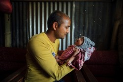"On 26 May, Narayan Krishna Shivakoti holds his crying 22-day-old son, Nirman, in a building in the earthquake-affected town of Singati, near the town of Charikot in Dolakha District, epicentre of the 12 May earthquake. Nirman was born in the period between the first and second earthquakes. ""Someday, when we look back, we won't remember this as a time of loss or earthquakes, but as when our first baby was born. And he is a healthy baby,"" Mr. Shivakoti said. He and his wife (Durga Shivakoti) lived about a kilometre from the quake's epicentre. Their home was destroyed and their poultry farm was damaged during the second disaster. UNICEF and partners are providing shelter, hygiene and nutrition supplies across quake-affected areas of the country. In late May 2015 in Nepal, recovery efforts continued following the 7.8-magnitude quake that struck on 25 April and the 7.3-magnitude quake that struck on 12 May. As of 27 May, more than 8,670 people have been killed and 21,933 people have been injured in the disaster. In the 14 districts hardest hit, 2.8 million people, including 1.1 million children, have been affected. Residences, schools and vital infrastructure, including hospitals, have also been severely damaged or destroyed in the disaster, leaving children and families homeless, vulnerable to disease outbreaks and in urgent need of food, shelter, safe water and sanitation, and health, protection and education support. UNICEF, working with the Government and other partners, is supporting efforts across vital sectors, including water, sanitation and hygiene (WASH), nutrition, health, child protection and education. By 20 May, UNICEF had reached approximately 305,109 people with water interventions and provided 45,201 people with access to sanitation and handwashing facilities and 225,585 people with hygiene education and related materials. Additionally, 122 child-friendly spaces have now been set up for displaced communities in eight districts, benefiting 12,200 a"