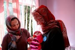重度の急性栄養不良になって治療を受けているアブドゥルマリクくんを抱く、ユニセフ・イエメン事務所代表(イエメン・サヌア:ユニセフが支援するアル・サビン病院にて)