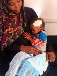 お母さんの腕に抱かれるアブドゥくん。栄養不良および脱水症状と診断されたが、通院にかかる費用が賄えず、治療の中断を余儀なくされていた。イエメン・サヌア:ユニセフが支援するアル・サビン病院にて)