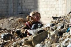 瓦礫の中笑顔を見せるシリアの女の子