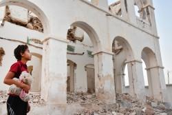人形片手に壊れた家を見上げる子ども(イエメン・ムカッラー)2016年3月撮影