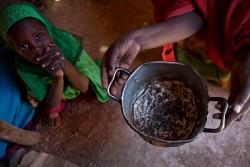 空の鍋を持ち上げる母親と女の子(ソマリア)2017年3月9日撮影