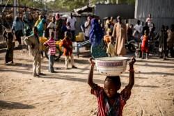 国内避難民キャンプで鍋に水を汲んで運ぶ女の子(ナイジェリア・マイドゥグリ)2017年3月2日撮影