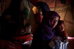 インフルエンザと下痢に苦しむ2人の子どもたちと母親(ソマリア・ブラオ)2017年3月8日撮影