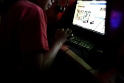 薄暗いインターネットカフェで自分のSNSをチェックする女の子(フィリピン・マニラ)2016年3月撮影