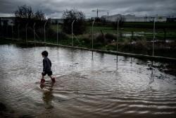 寒い中、難民キャンプで水遊びをする男の子(ギリシャ・ハルキス)2017年3月10日撮影