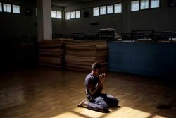 人の同伴者のいない子どものための施設で、祈りをささげる男の子(イタリア・シチリア島)2016年5月撮影