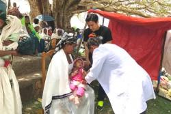 村の子どもたちに、はしかワクチンが接種される様子を見守る長谷部選手。