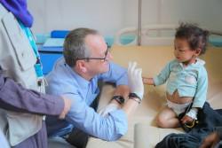コレラが疑われる症状のある子どもとユニセフ中東・北アフリカ地域事務所代表ヘルト・カッペラエレ (イエメン・サヌア)