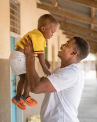 生後1歳10カ月の息子を抱き上げるお父さん(ウガンダ)。