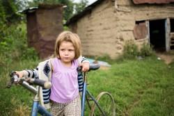 タイヤのない古い自転車で遊ぶ4歳の女の子 (ルーマニア)2016年8月撮影