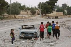 破壊された車の脇を歩く子どもたち。(2017年5月18日撮影)