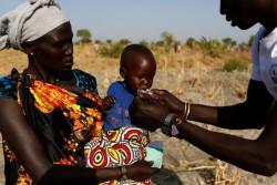 2歳の女の子にプランピーナッツを与えるユニセフの栄養保健員(南スーダン・レール郡) 2017年2月26日撮影